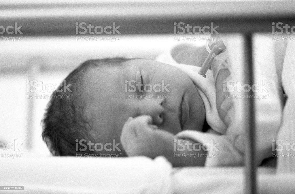 Close-up black and white image of sleeping new born baby boy,...