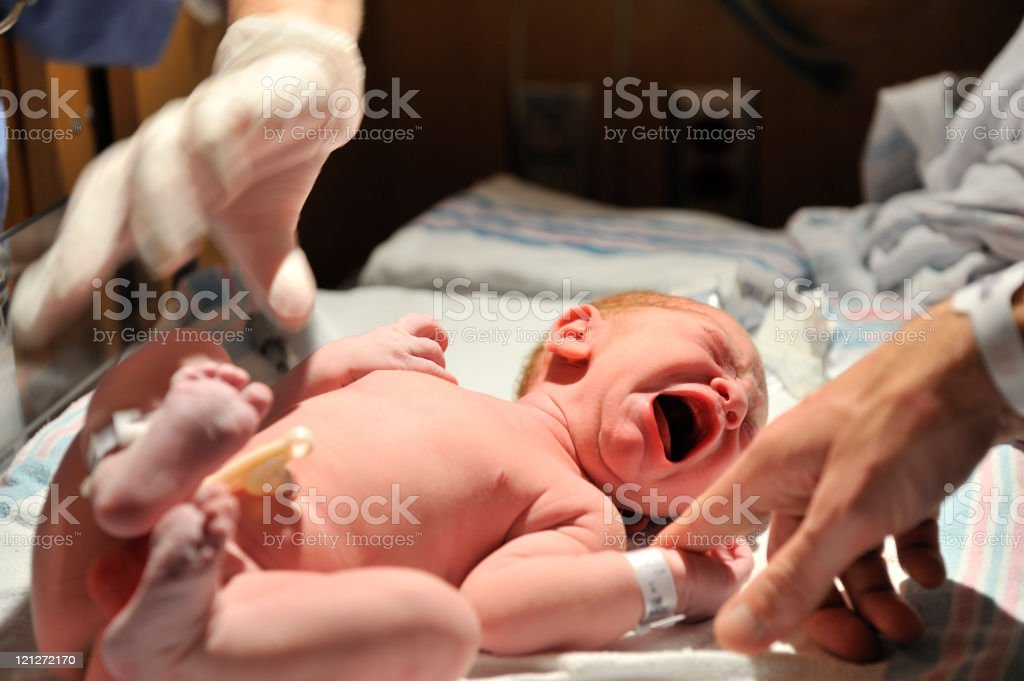A new born baby kicking and crying royalty-free stock photo