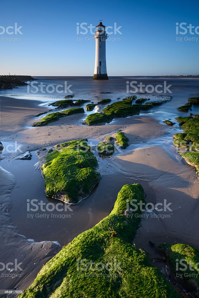 New Brighton lighthouse with green rocks foreground stock photo