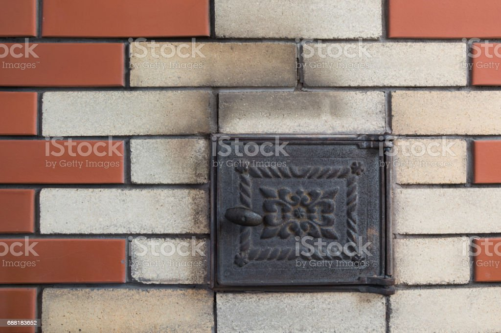 New brown brick wall with rusty door furnace. Abstract. Pattern. stock photo