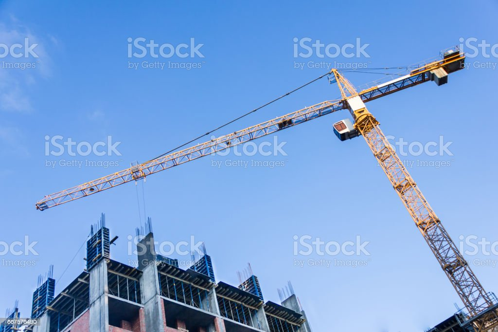 A new building is being constructed with use of tower crane. Jib stock photo