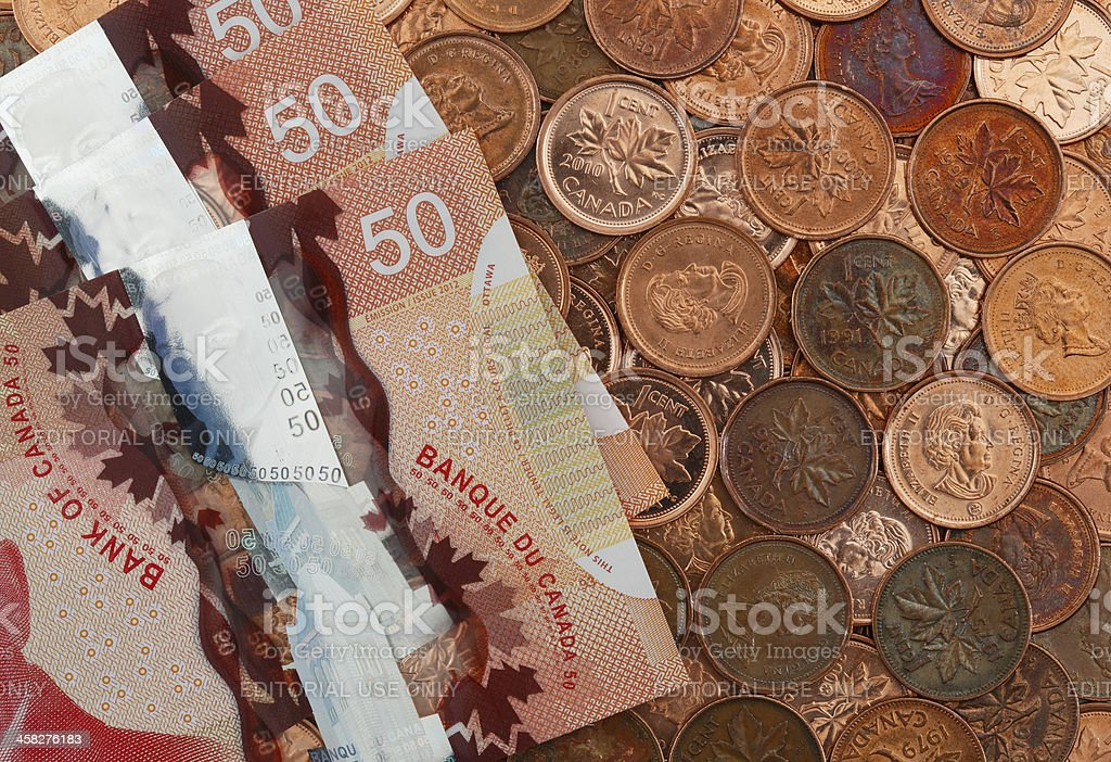 New Canadian Fifty Dollar Bills On A Bed Of Pennies royalty-free stock photo