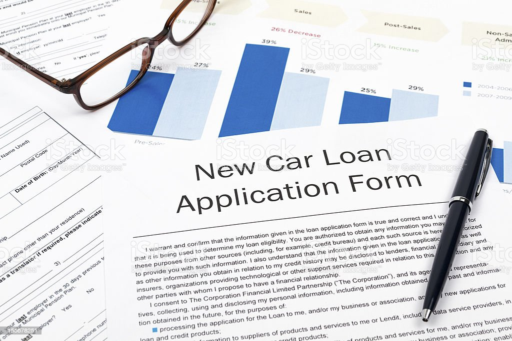 New car loan application form on top of other documents stock photo