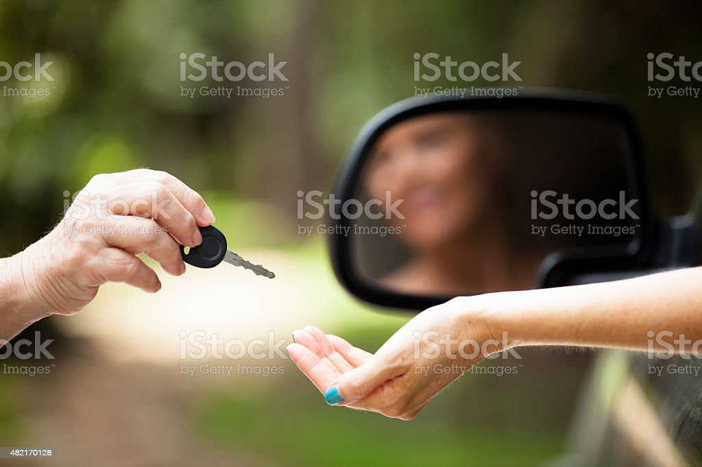 New car. Salesperson gives vehicle key to woman buyer, driver. stock photo