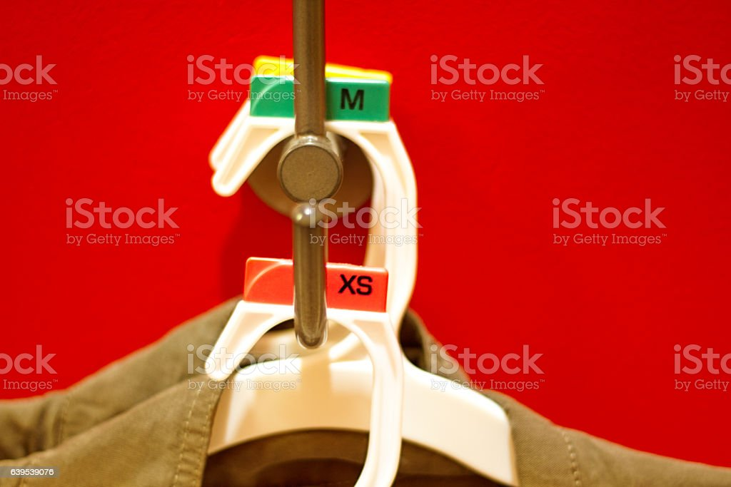 New Clothes Hanging on Red Wall in Dressing Room (Close-Up) stock photo