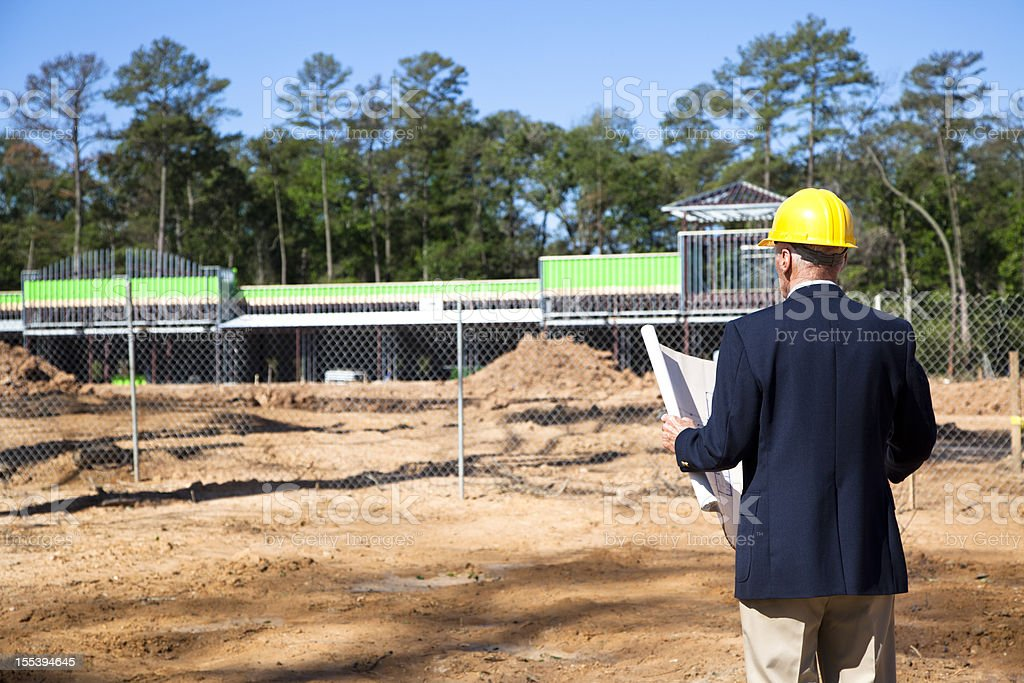 New commercial building construction site with contractor in foreground stock photo