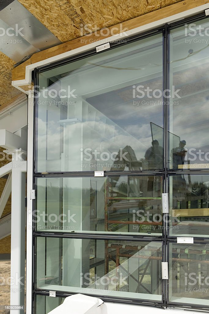 New Commercial Window Installation with Workers Reflected in Glass royalty-free stock photo