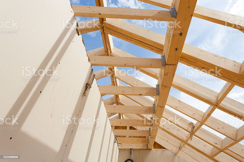 New construction home framing against blue sky stock photo