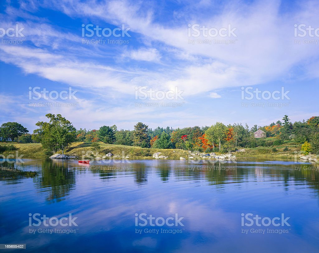 New England autumn pond with small red boat. Maine royalty-free stock photo