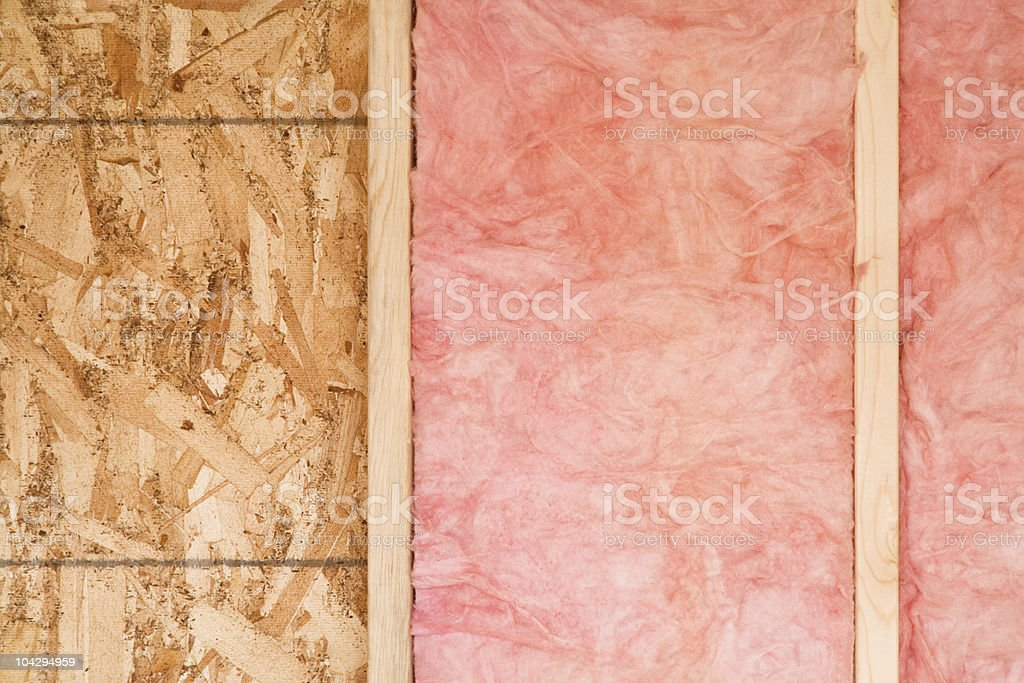 New exposed wall showing pink fiberglass insulation stock photo