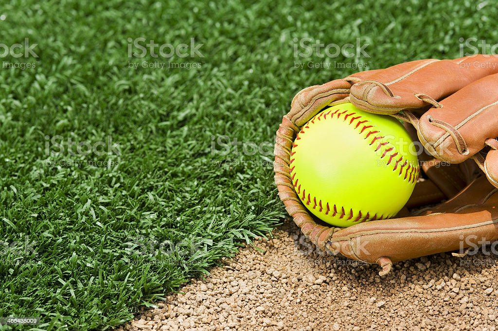 A New \'Fast Pitch\' Softball in a glove sitting between the infield...