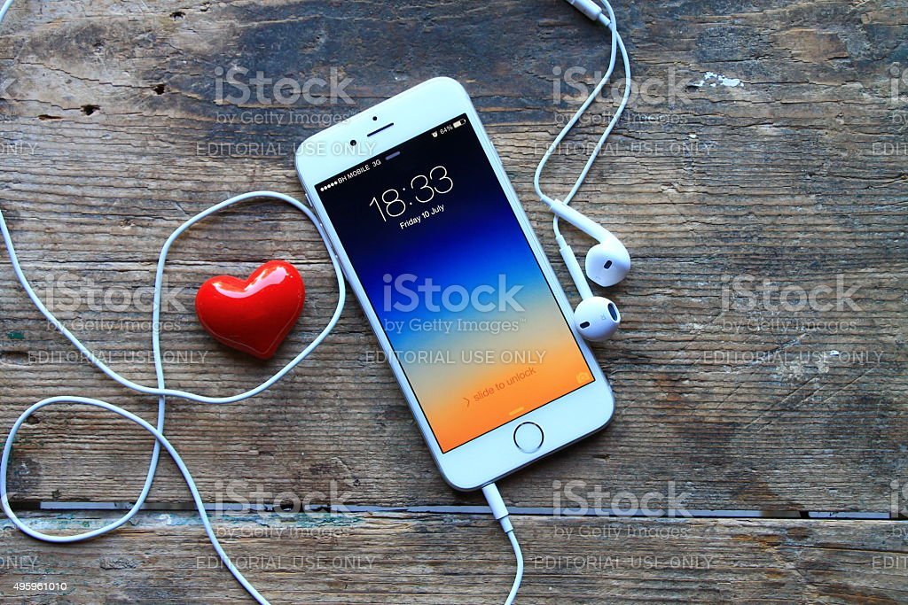 New gray iphone 6 and red heart on wooden table stock photo