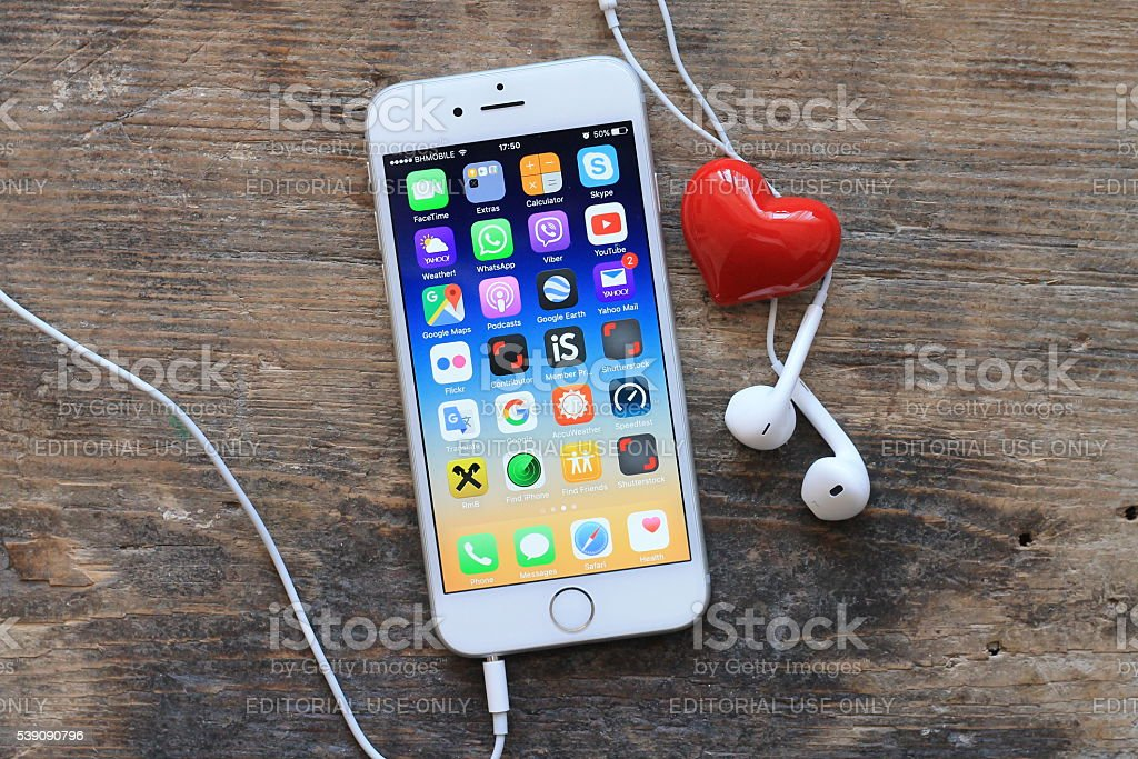 New gray iphone 6 and red heart on wooden table. stock photo