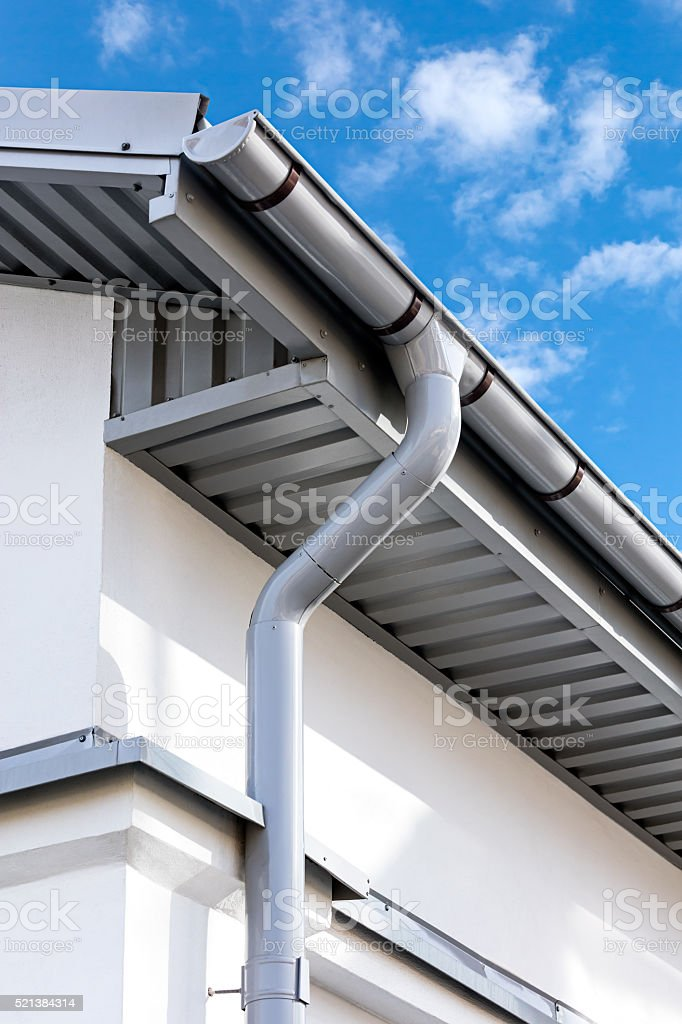 new gray metal rain gutter on house rooftop stock photo