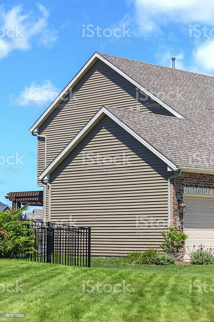 New Home showing Vinyl Siding, Yard, Wrought Iron Fence royalty-free stock photo
