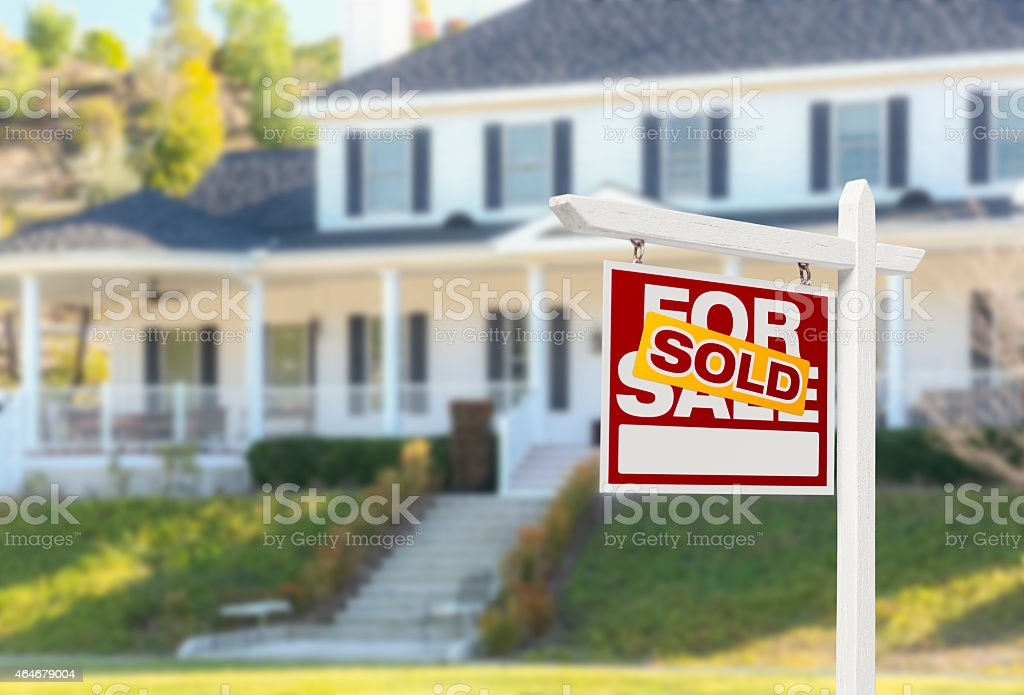 New home with sold stamped across the for sale sign in yard stock photo