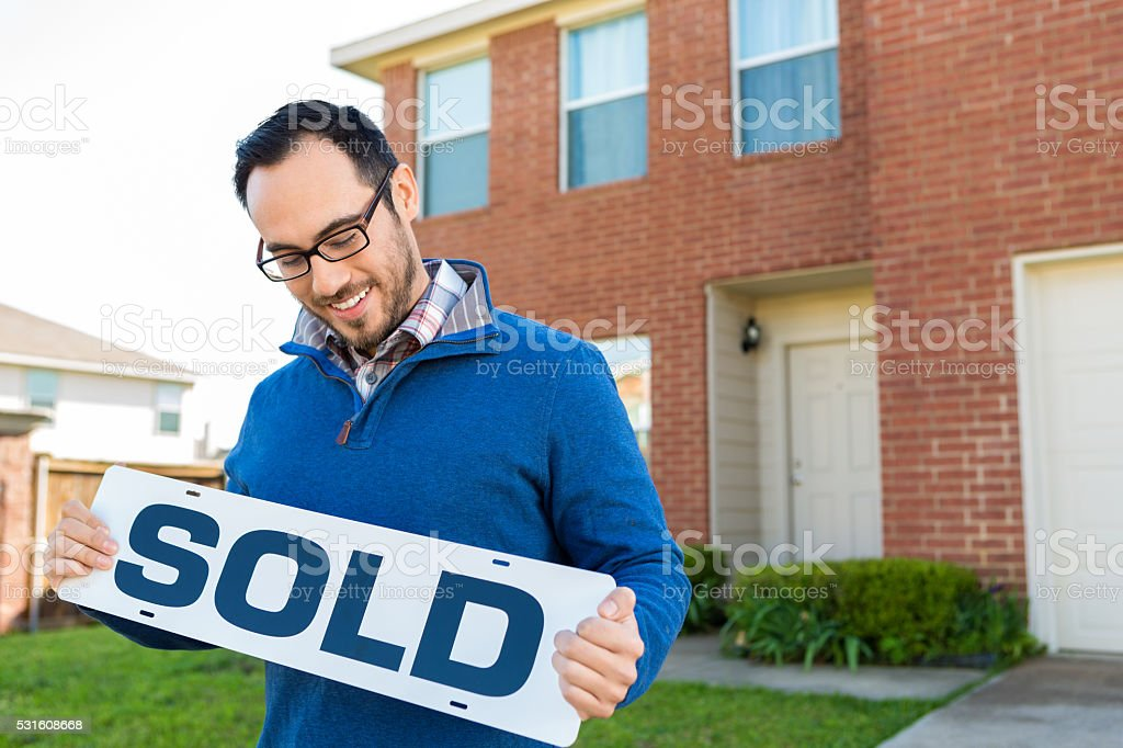 New homeowner in front of two story home stock photo