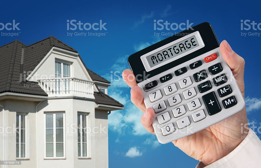 New House and Hand with Mortgage Calculator royalty-free stock photo