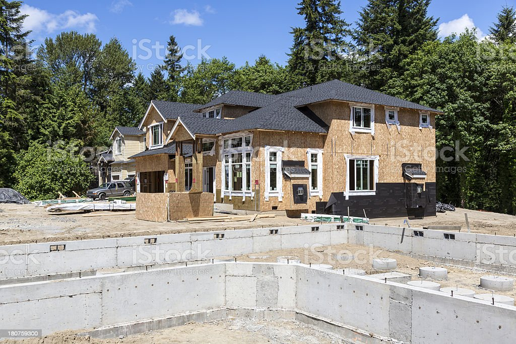 New house foundation with partially complete in background stock photo