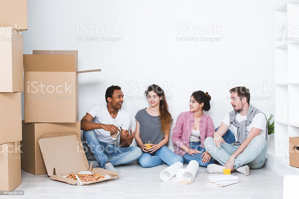 New house. Friends sitting on floor after unpacking. stock photo