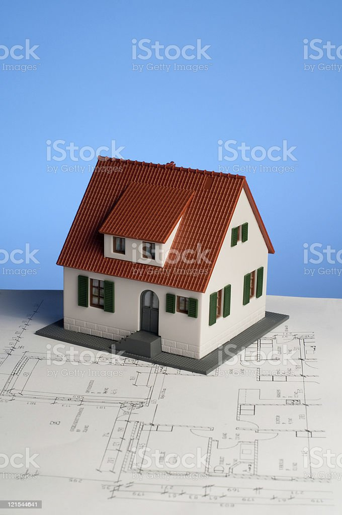 New house is being planned with minature home on blueprint royalty-free stock photo
