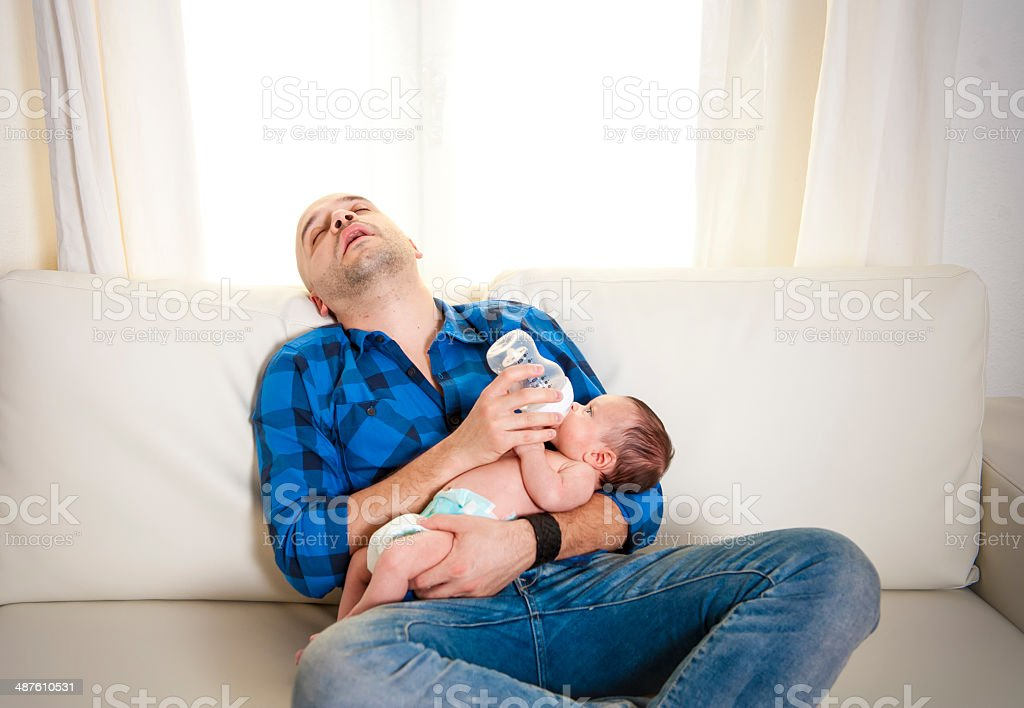 new latino father alseep while feeding his newborn baby stock photo