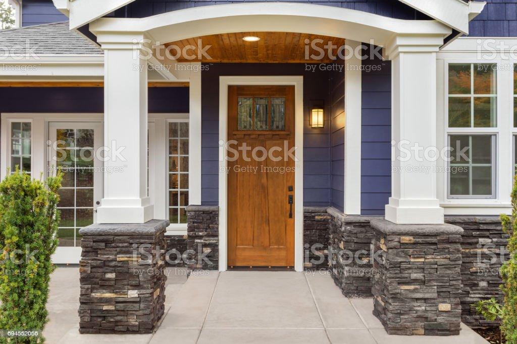 new luxury home exterior detail: patio and front door with arch and columns. Stonework graces the bottom of the columns and house while white columns and archway provide a stately welcome stock photo