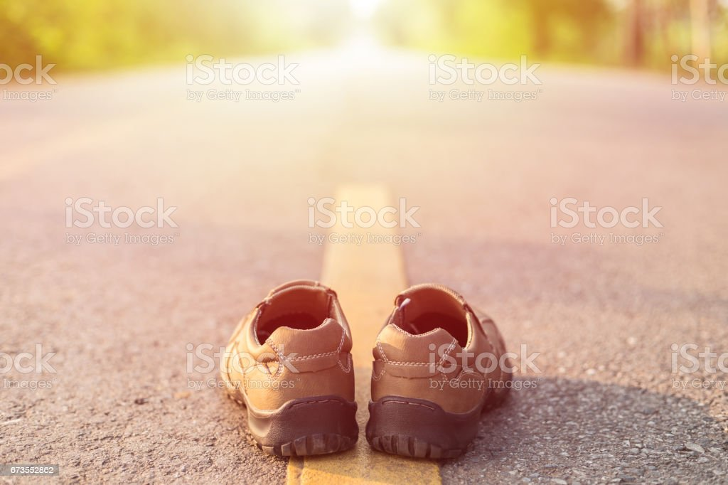 New men fashion shoes on asphalt road beside yellow stripe stock photo