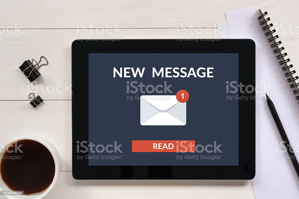 New message concept on tablet screen with office objects stock photo