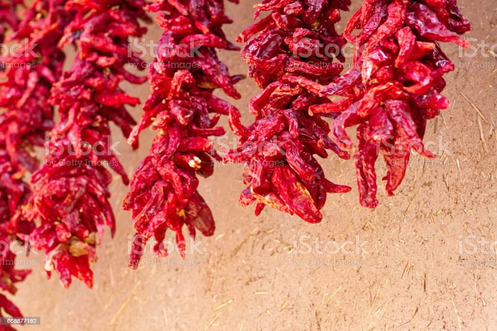 New Mexico: Chili Pepper Ristras On Raw Adobe Wall stock photo