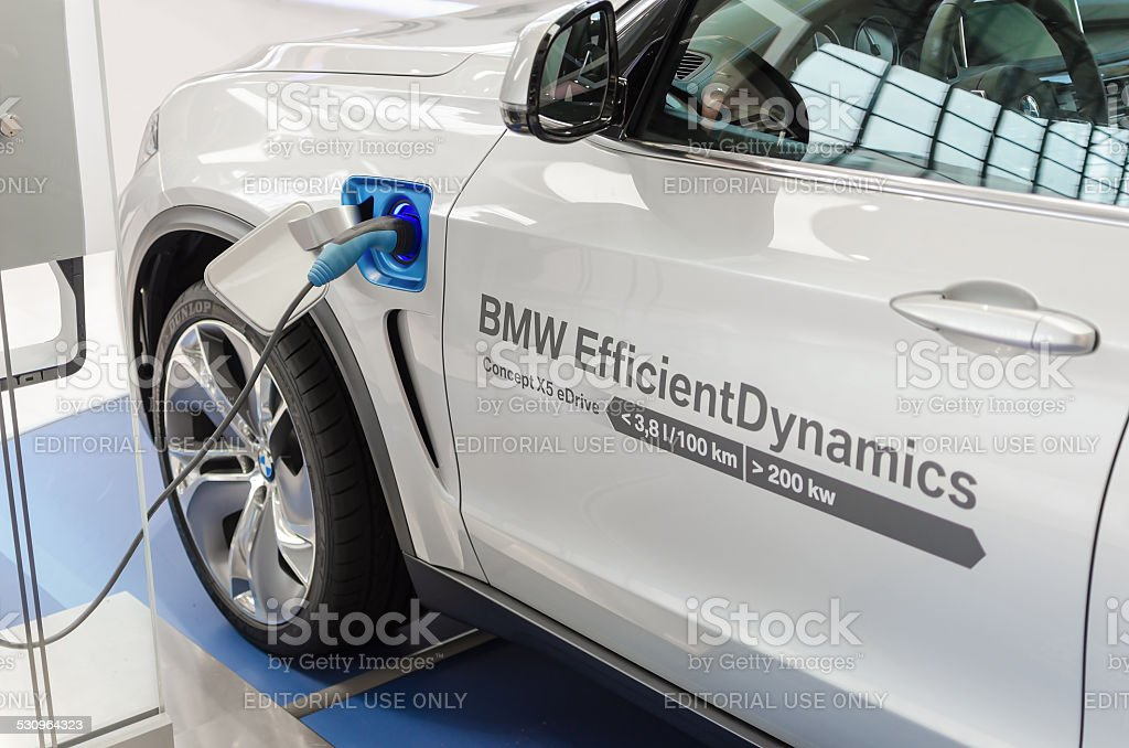 New model BMW x5 with hybrid engine at charging station stock photo