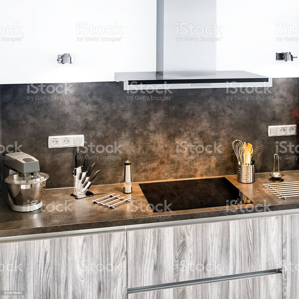 New modern gray kitchen with utensils next to range hood stock photo