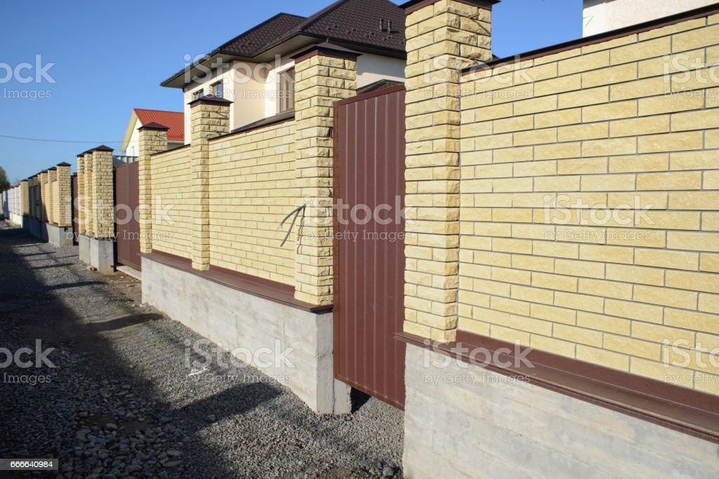 New modern yellow high metal fence in early spring stock photo