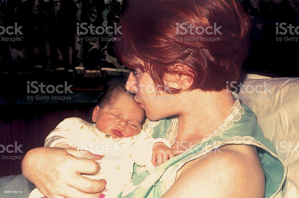 New mom kissing her newborn baby stock photo