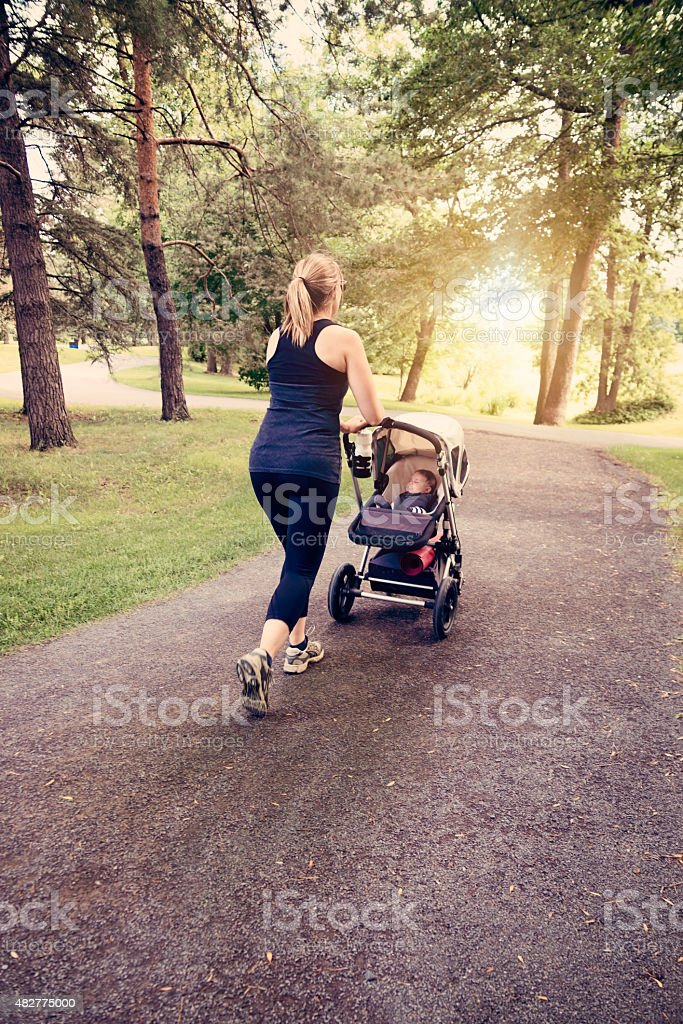 New mother jogging with stroller in public park. stock photo
