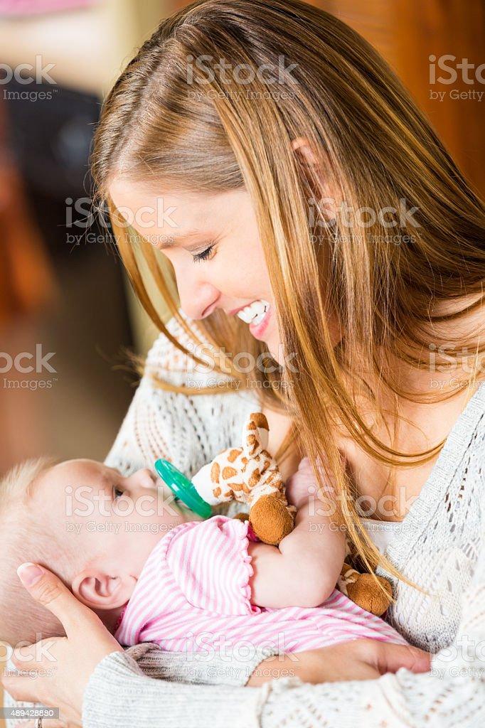 New mother rocking and cuddling newborn daughter stock photo