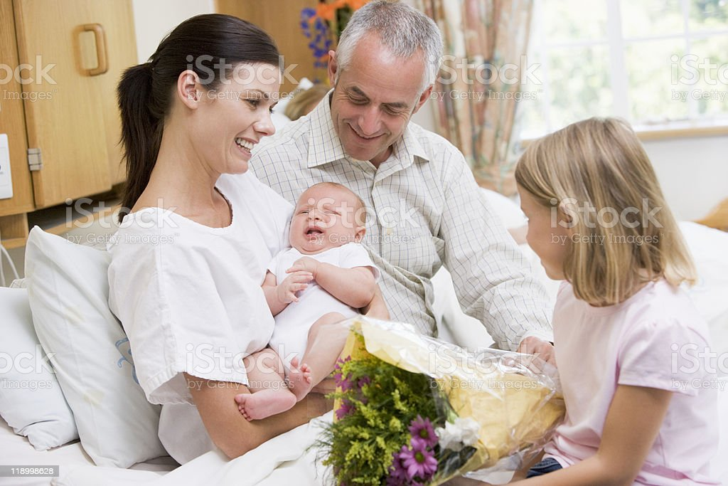 New mother with baby and family in hospital stock photo