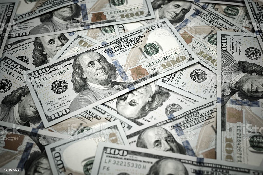 New one hundred dollar bills piled on top of each other stock photo
