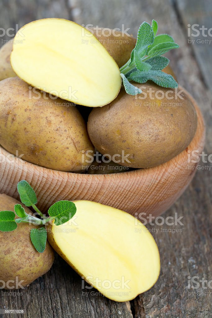new potato in a wooden bowl stock photo