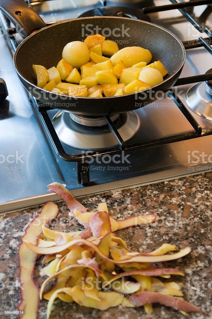 new potatoes frying in pan with the peels in foreground stock photo