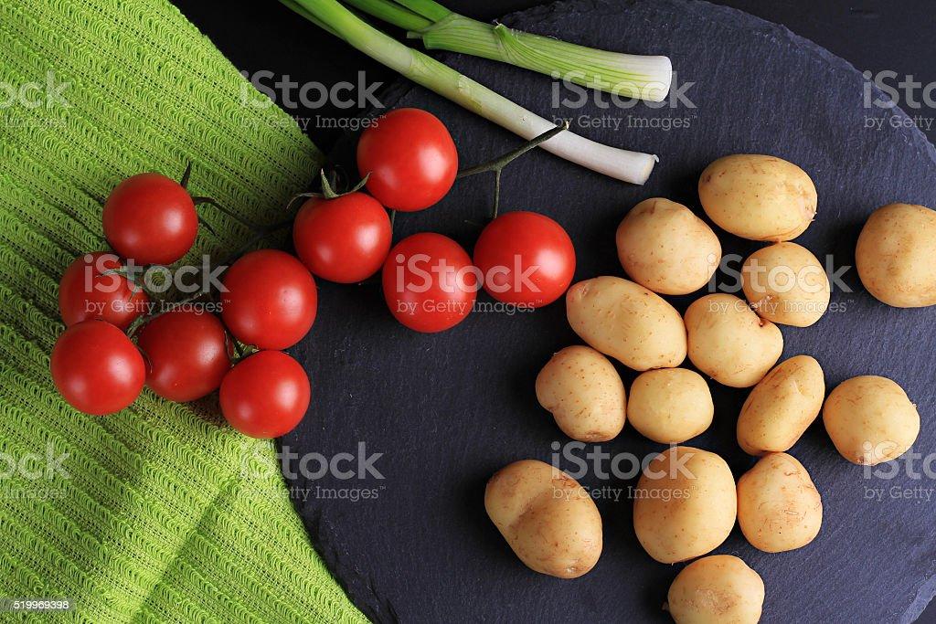 New potatoes, green onion, cherry tomatoes stock photo