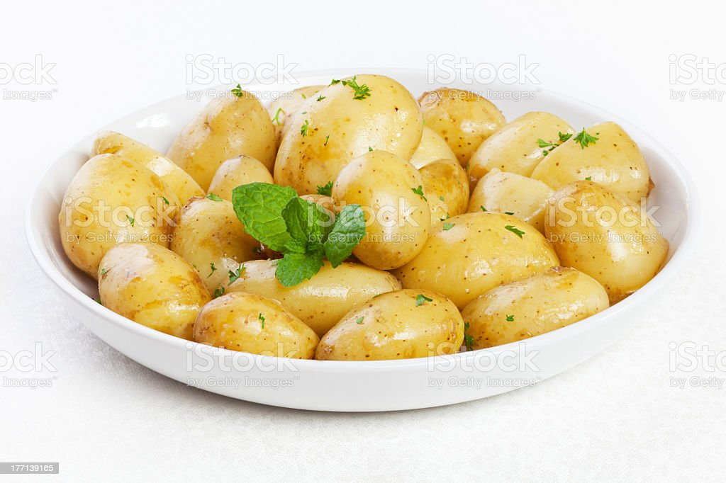 New potatoes in butter with parsley and mint stock photo