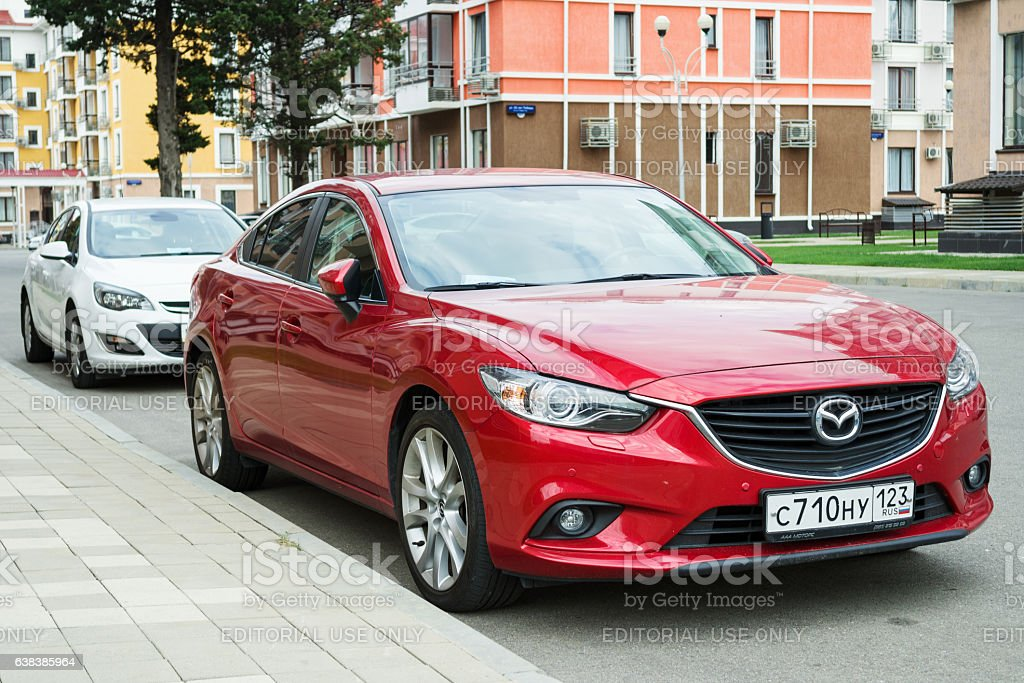 New red Mazda 6 parked near modern houses. stock photo