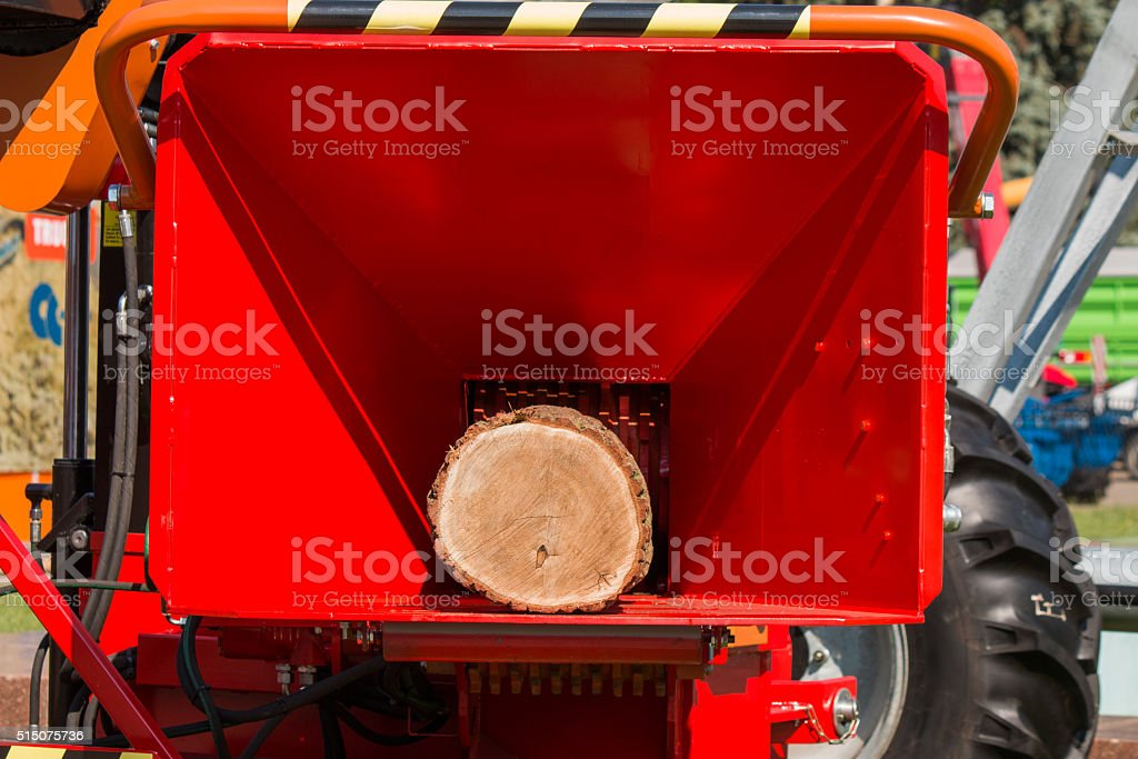 new red receiving mouth of wood chipper with demonstration log stock photo