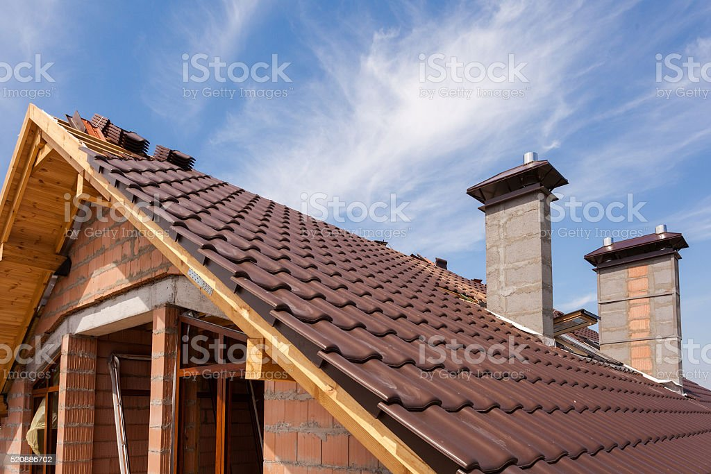New red tiled Roof with chimneys and skylight stock photo