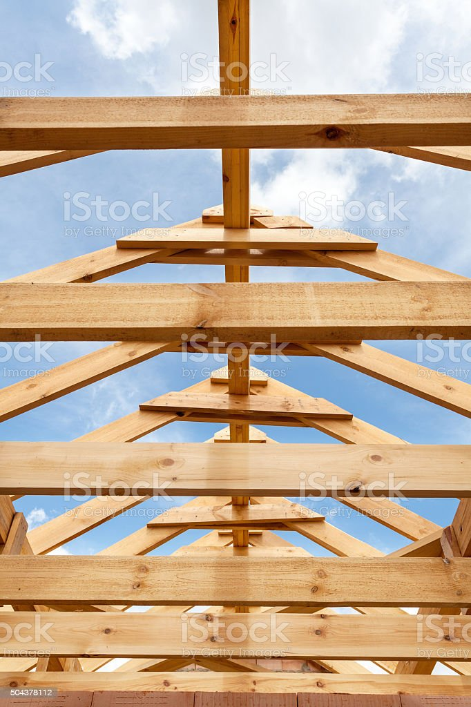 New residential wooden construction home framing against a blue sky stock photo