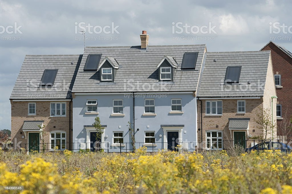 New row of houses in England viewed over meadow royalty-free stock photo