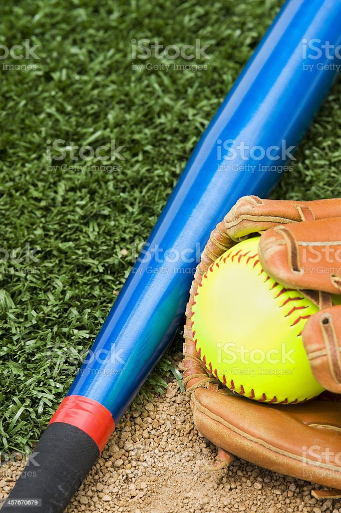 A New \'Fast Pitch\' Softball in a glove,with an aluminum bat sitting...