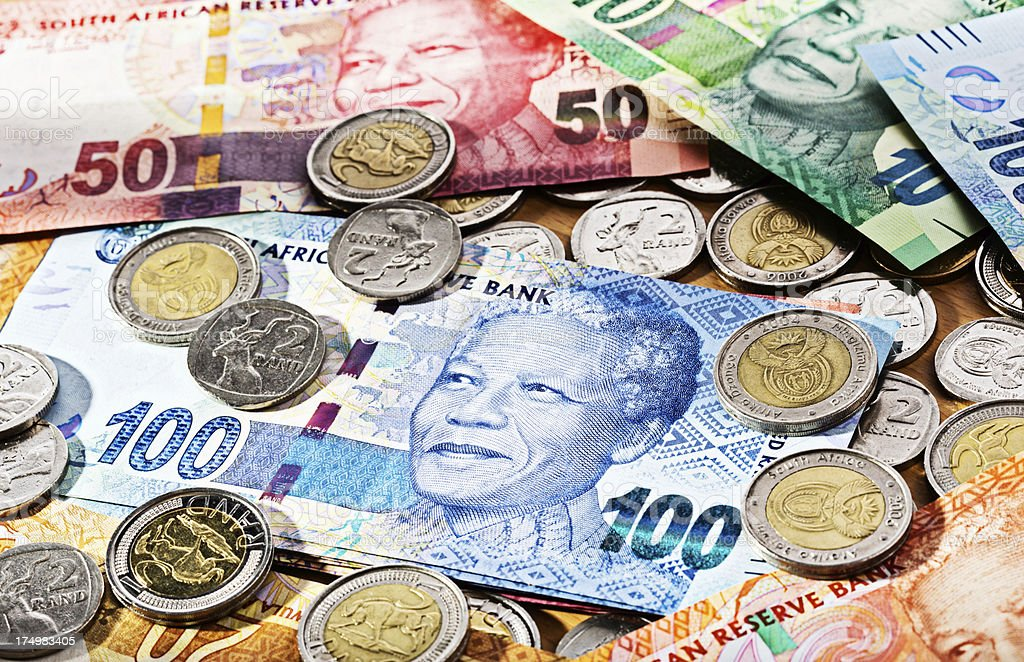 New South African banknotes and coins spread out over desk stock photo