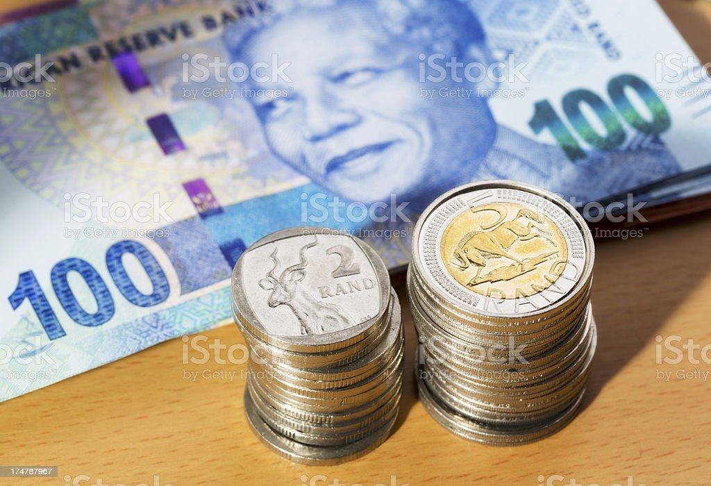 New South African banknotes, featuring Mandela, plus piles of coins royalty-free stock photo